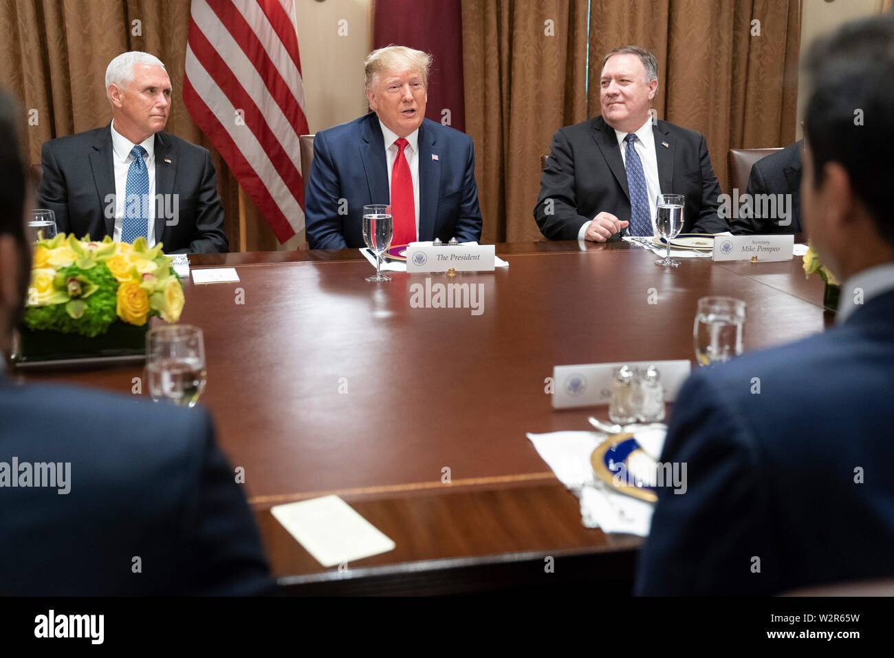 U.S President Donald Trump, joined by Vice President Mike Pence, left, and Secretary of State Mike Pompeo, right, participate in an expanded working luncheon with the Emir of Qatar, Tamin bin Hamad Al Thani and delegates at the Cabinet Room of the White House July 9, 2019 in Washington, DC. - Stock Image