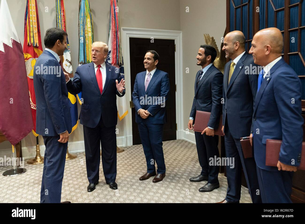 U.S President Donald Trump chats with the Emir of Qatar Tamin bin Hamad Al Thani, left, and members of his delegation in the Roosevelt Room of the White House July 9, 2019 in Washington, DC. - Stock Image