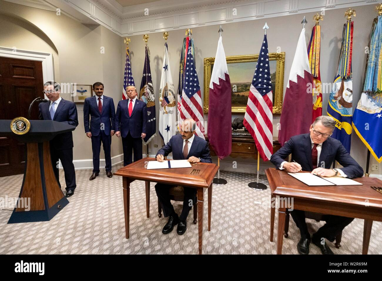 U.S President Donald Trump, stands next to the Emir of Qatar, Tamin bin Hamad Al Thani as they watch the signing of a commercial agreement in the Roosevelt Room of the White House July 9, 2019 in Washington, DC. U.S Treasury Secretary Steve Mnuchin, left, addresses the delegation. - Stock Image
