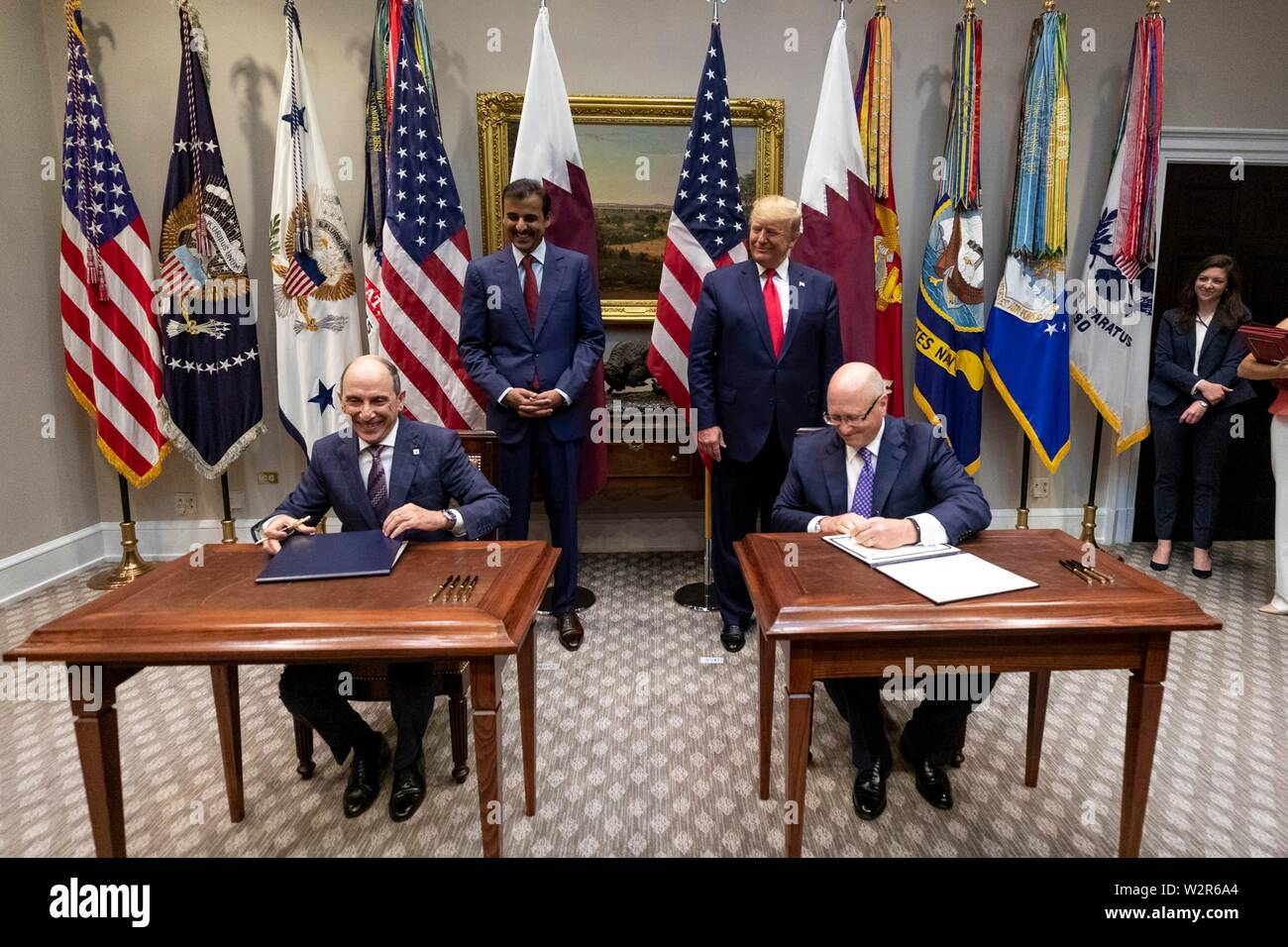 U.S President Donald Trump, stands next to the Emir of Qatar, Tamin bin Hamad Al Thani as they watch the signing of a commercial agreement in the Roosevelt Room of the White House July 9, 2019 in Washington, DC. - Stock Image