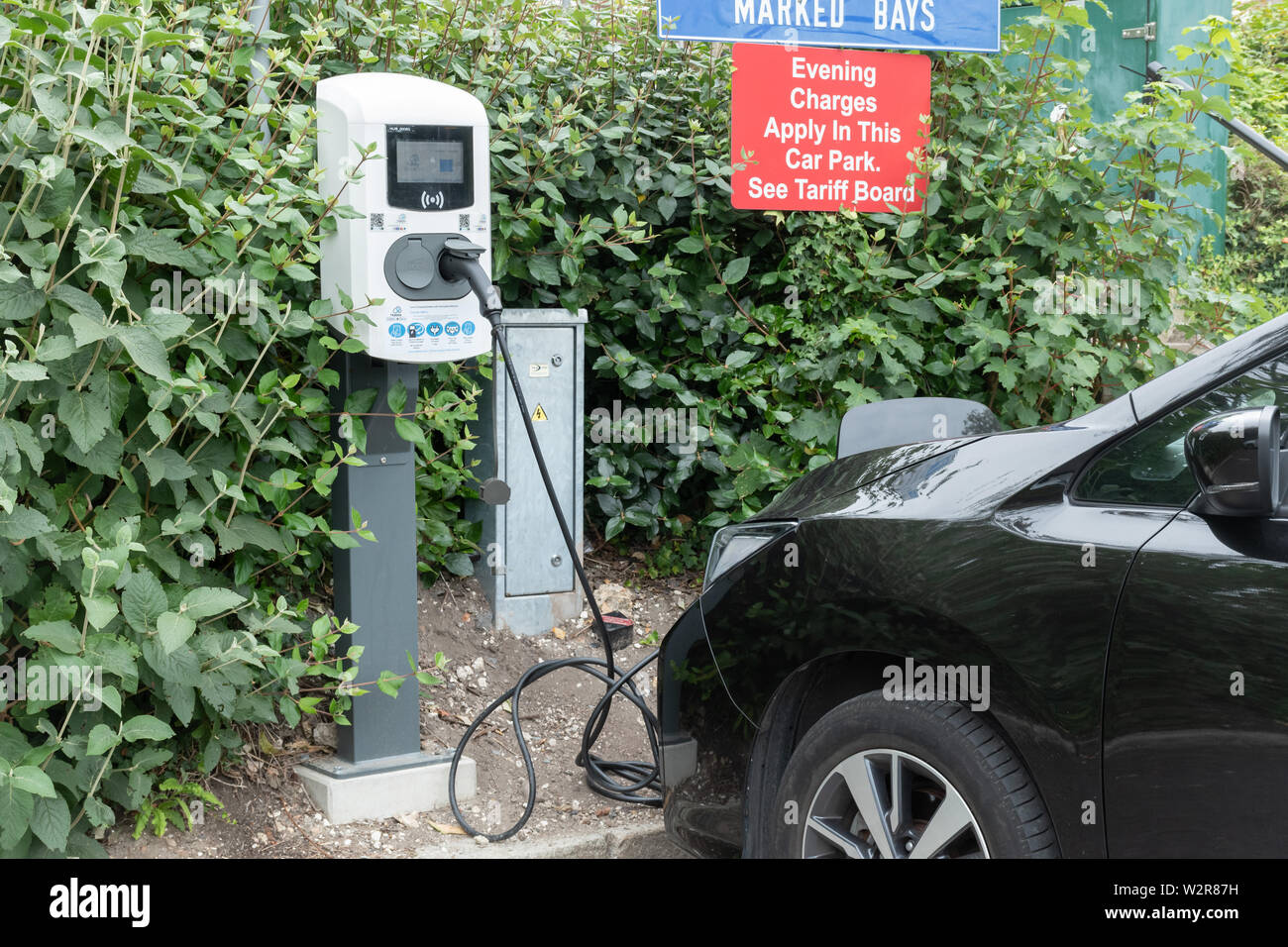 Electric car being charged in a public car park, UK. Electric charging point. Stock Photo