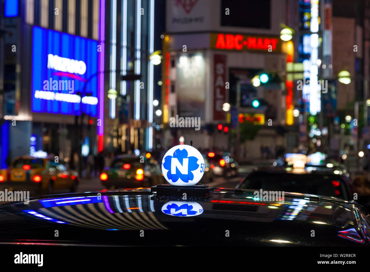 Roof of taxi and neon advertising signs at night in Shinjuku District, Tokyo, Japan. - Stock Image