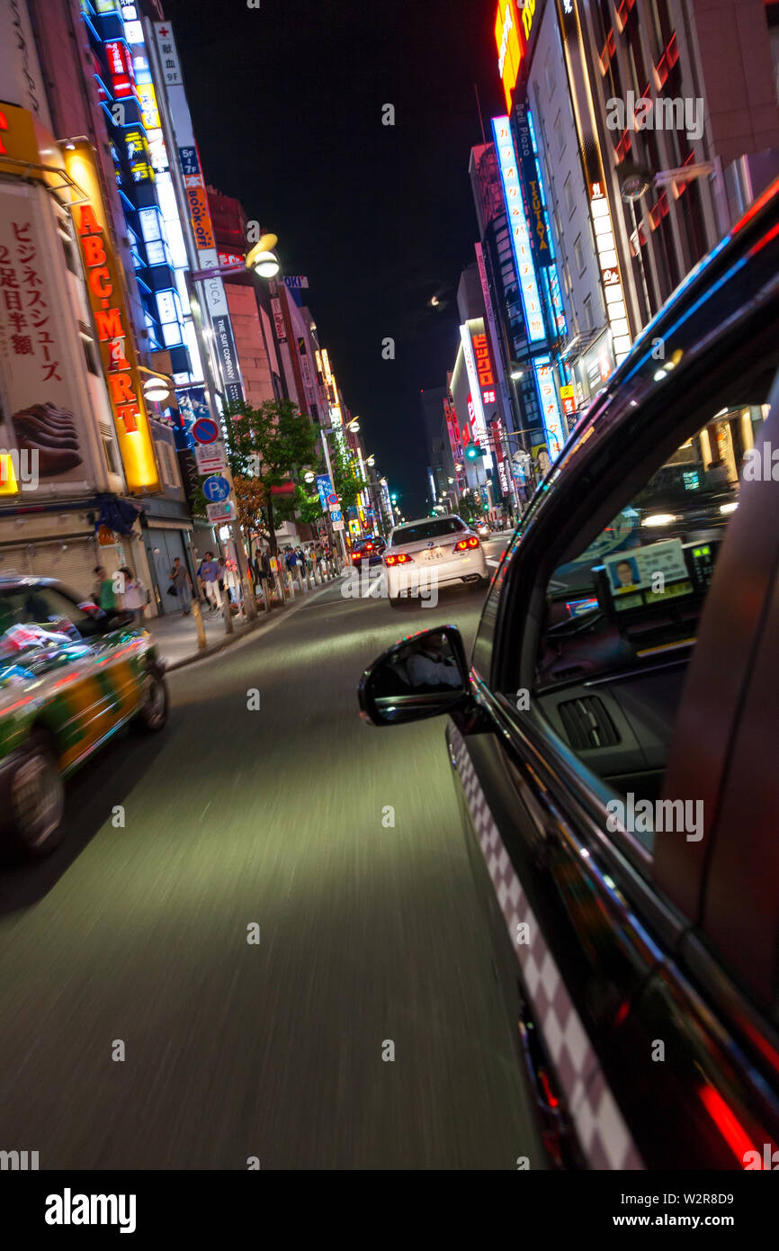 Motion blurred view from taxi of street and neon advertising signs at night in Shinjuku District, Tokyo, Japan. - Stock Image