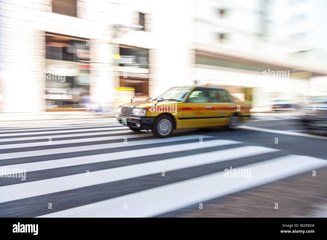 Motion blurred shot of yellow taxi cab on pedestrian crossing, Tokyo, Japan. - Stock Image