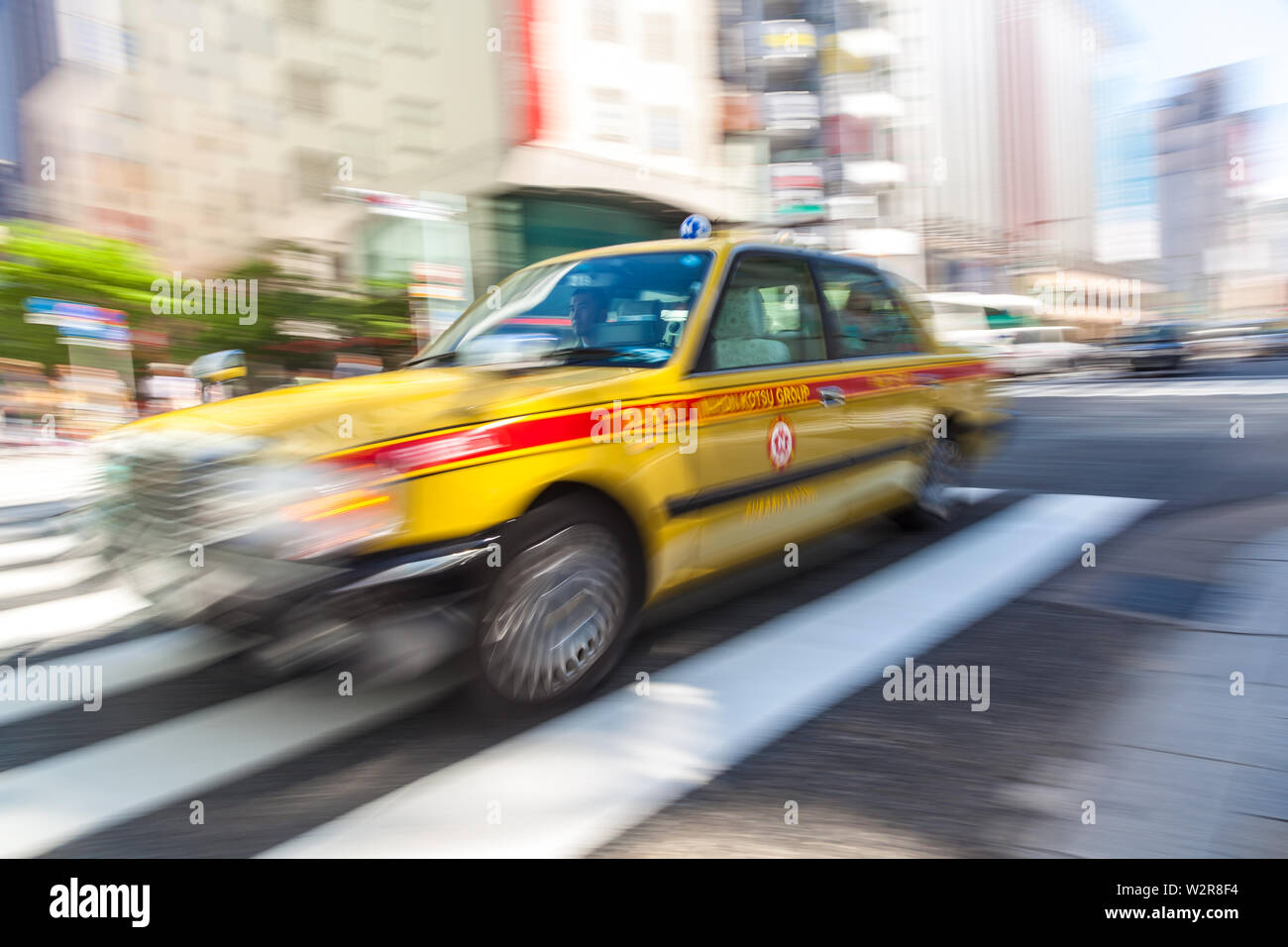 TOKYO, JAPAN – JUNE 06 2015: Motion blurred yellow taxi cab on pedestrian crossing, Tokyo, Japan. - Stock Image