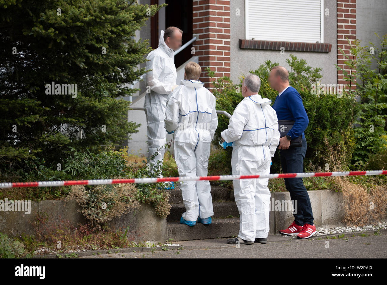 Werther, Germany. 10th July, 2019. Forensics officers are standing outside a house. Three dead were found in a detached house in Werther near Bielefeld. They were adults, a spokeswoman for the Gütersloh district police said on Wednesday. 'It doesn't look like an accident,' she continued. Credit: Friso Gentsch/dpa - ATTENTION: persons were pixelated for legal reasons/dpa/Alamy Live News - Stock Image