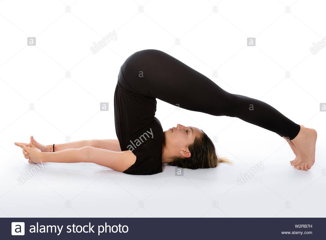 Halasana yoga pose (Plow Pose). Yoga poses woman isolated with white background. Yoga pose set. Mindfulness and Spiritually concept. Girl practicing H - Stock Image