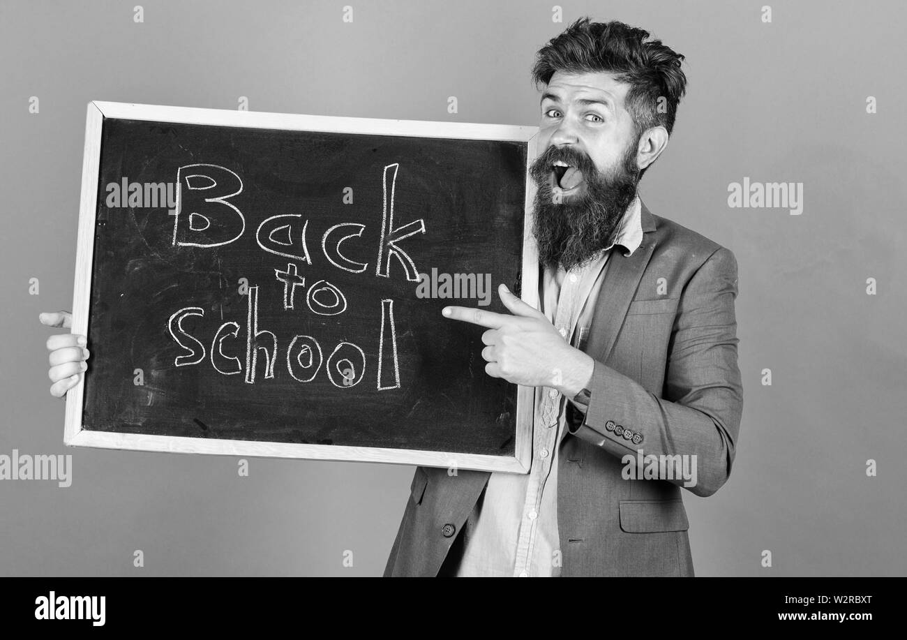 Man bearded in formal wear holds blackboard with text back to school. School season advertisement. Clothing for teachers. Man teacher classic clothing jacket and shirt stand over violet background. - Stock Image