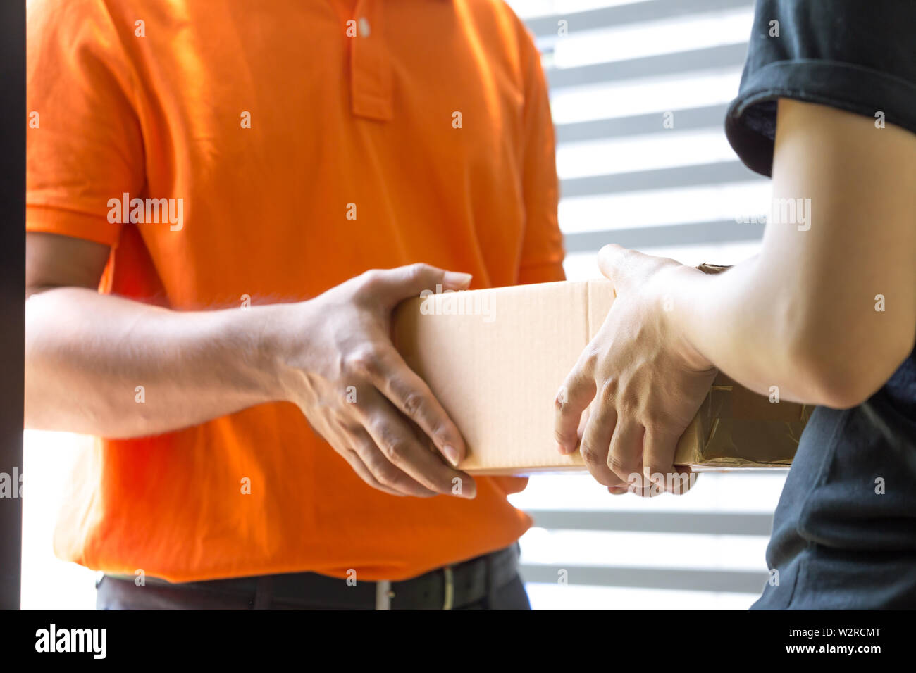 Woman hand accepting a delivery of boxes from deliveryman. Home delivery courier service and shipment concept - Stock Image