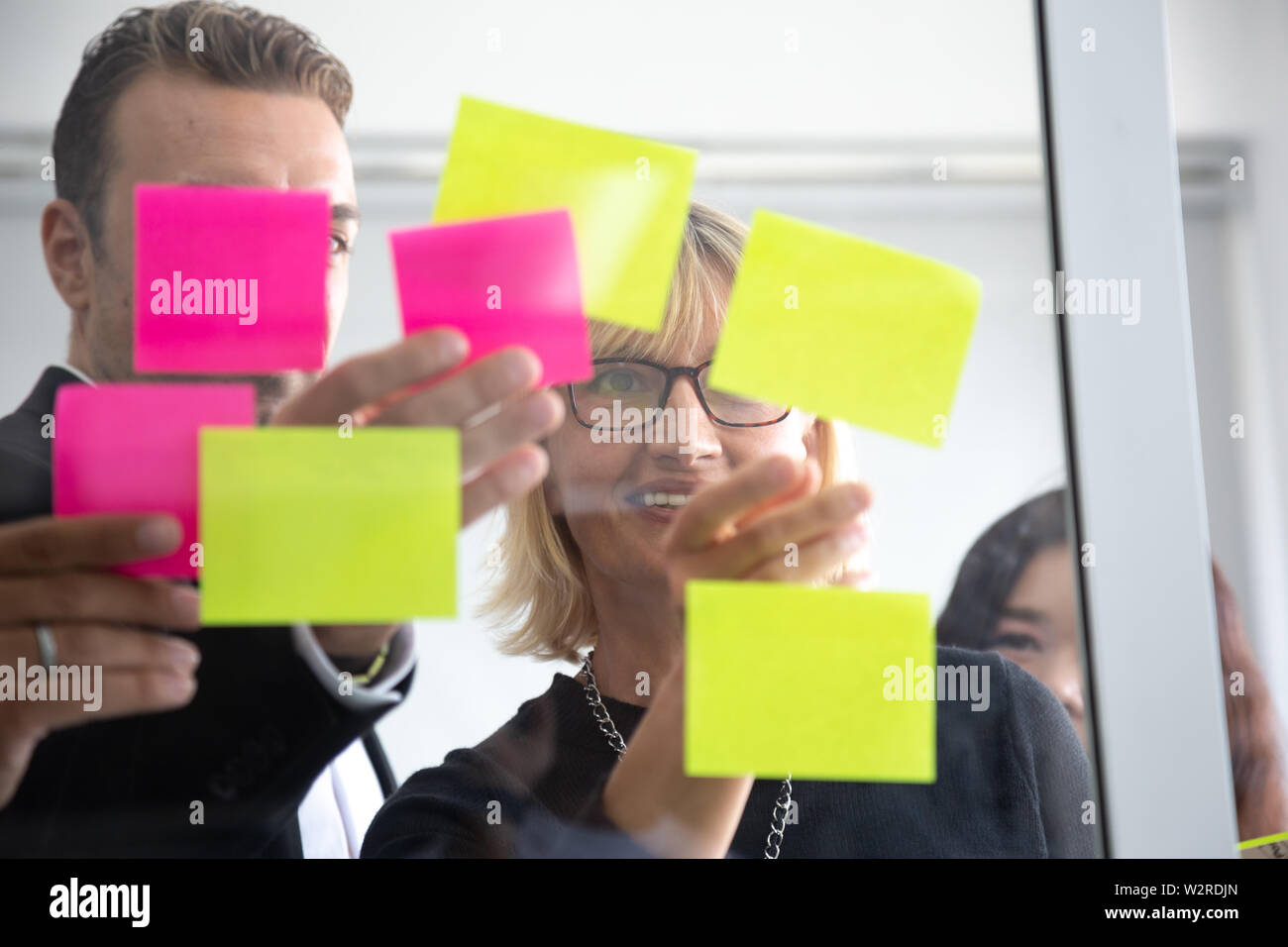 IT worker tracking his tasks on kanban board. Using task control of agile development methodology. Team members attaching sticky note to scrum task bo - Stock Image