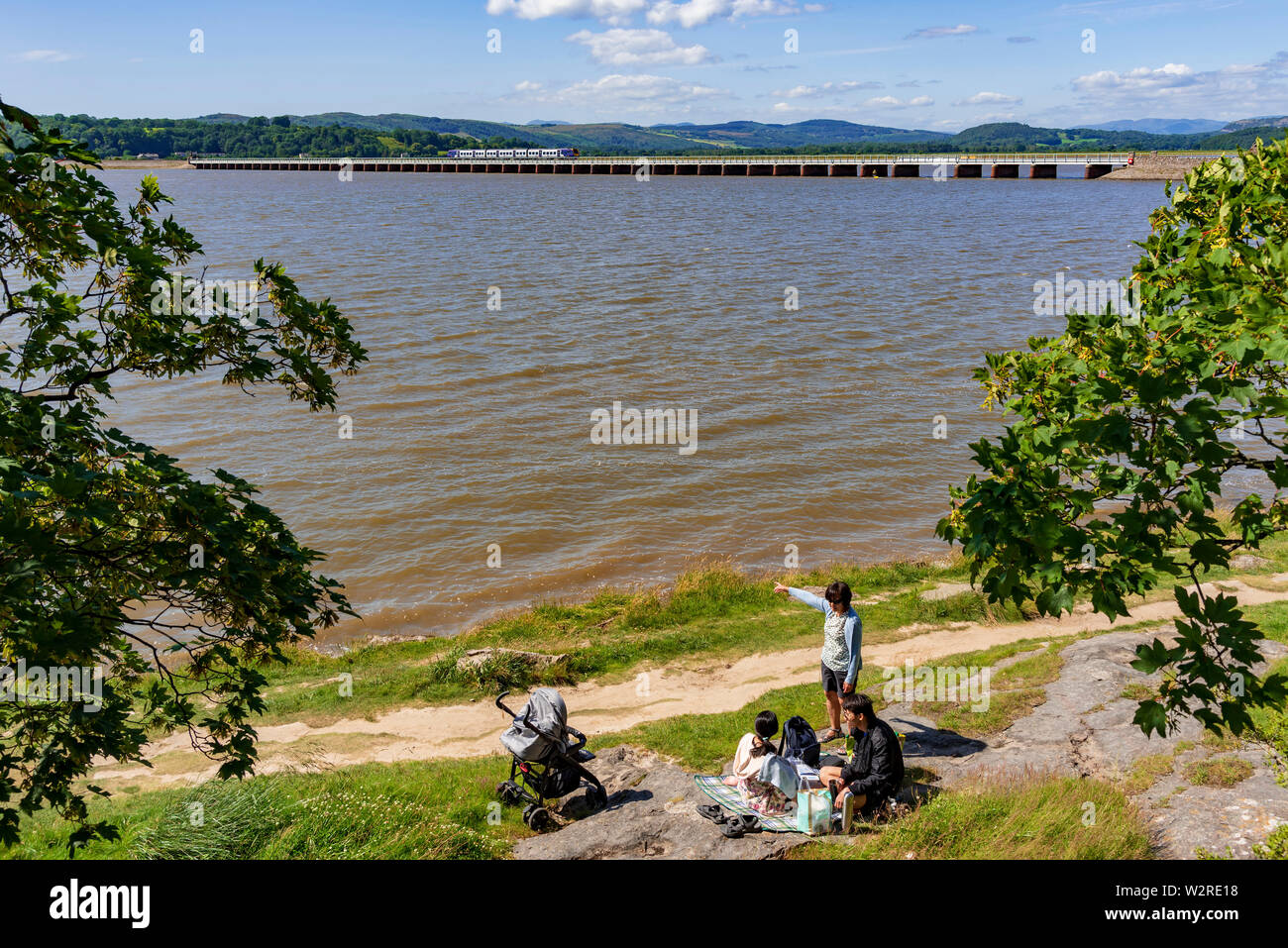 The railway viaduct over the river Kent at Arnside in Cumbria with picnicking family. - Stock Image