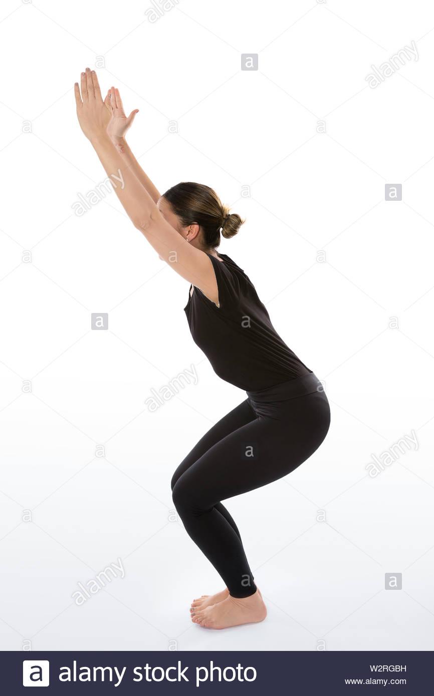 Utkatasana pose. Yoga poses woman isolated with white background. Yoga pose set. Mindfulness and Spiritually concept. Girl practicing Hatha Yoga asana - Stock Image