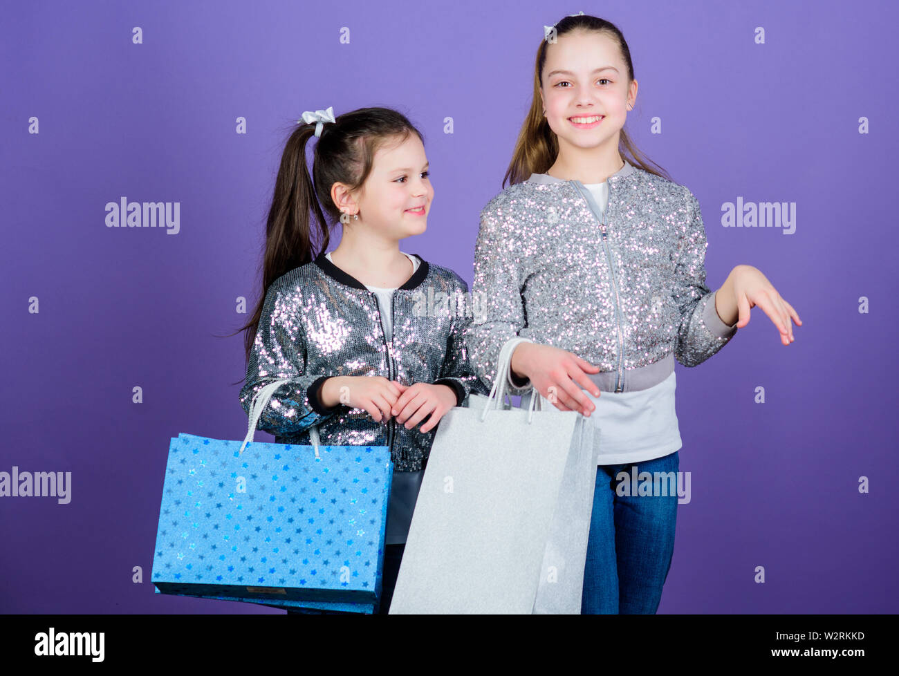 Discover something new. Girls sisters friends with shopping bags violet background. Shopping and purchase. Black friday. Sale and discount. Shopping day. Children bunch packages. Kids fashion. - Stock Image