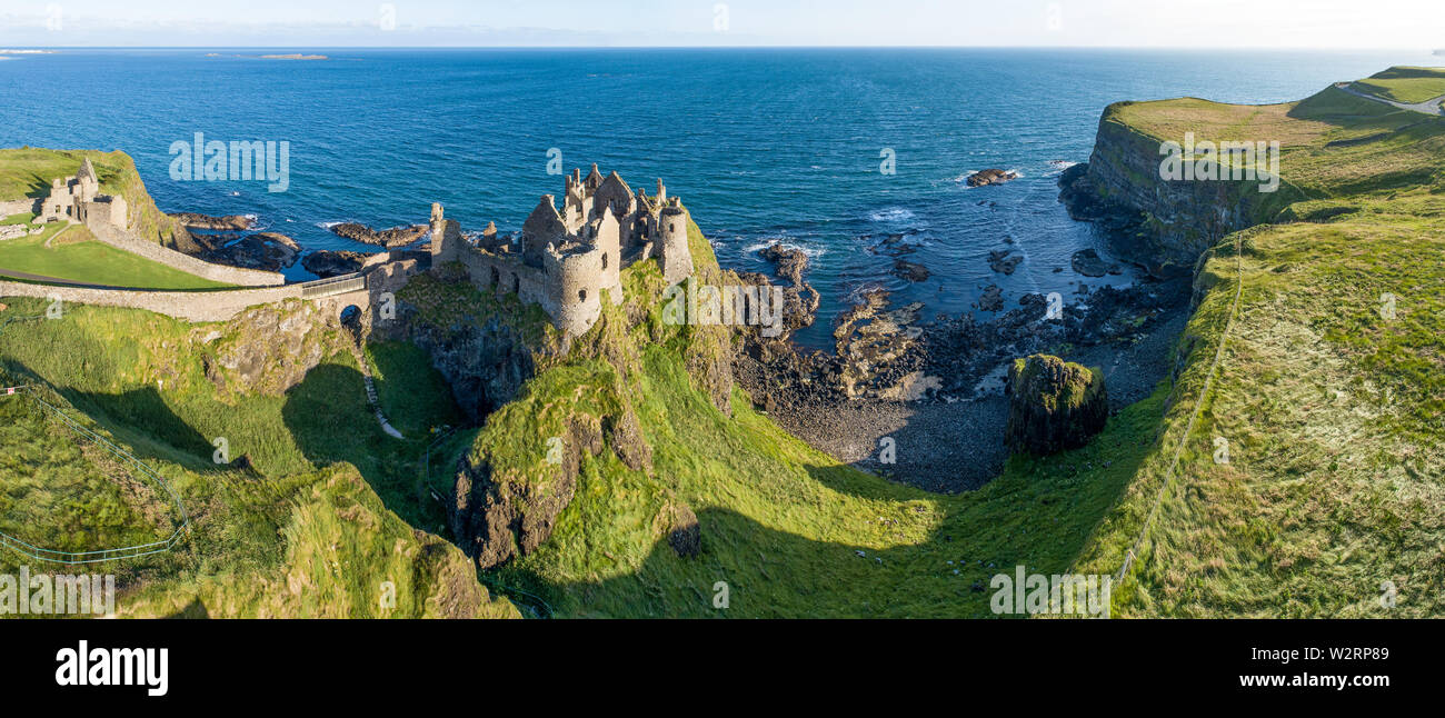Ruins of medieval Dunluce Castle on a steep cliff. Northern coast of County Antrim, Northern Ireland, UK. Aerial wide panorama in sunrise light - Stock Image