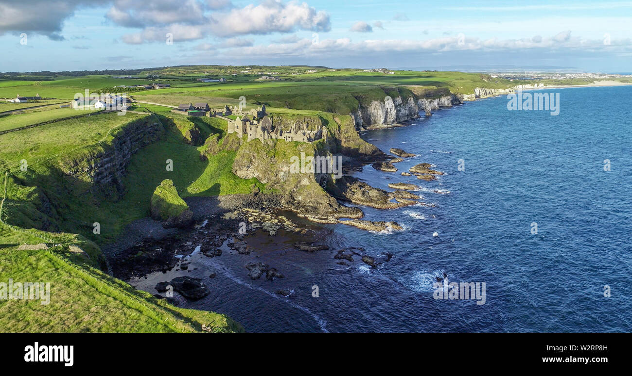 Ruins of medieval Dunluce Castle on a steep cliff near Bushmills. Northern coast of County Antrim, Northern Ireland, UK. Aerial view in sunrise light. - Stock Image