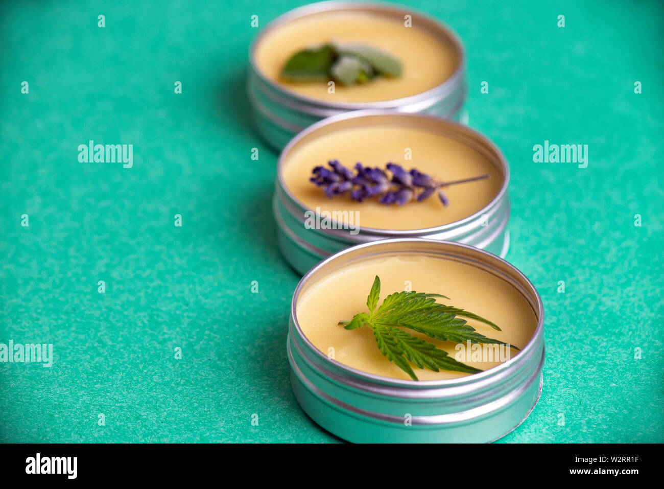 Cannabis salve made from hemp and CBD oils with mint, lavender and marijuana leaves on green background Stock Photo