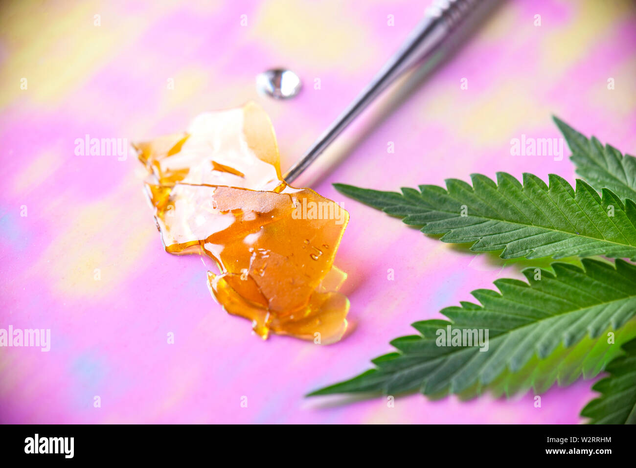Macro detail of dab tool with cannabis concentrate aka shatter and marijuana leaf, cannabis extraction concept Stock Photo