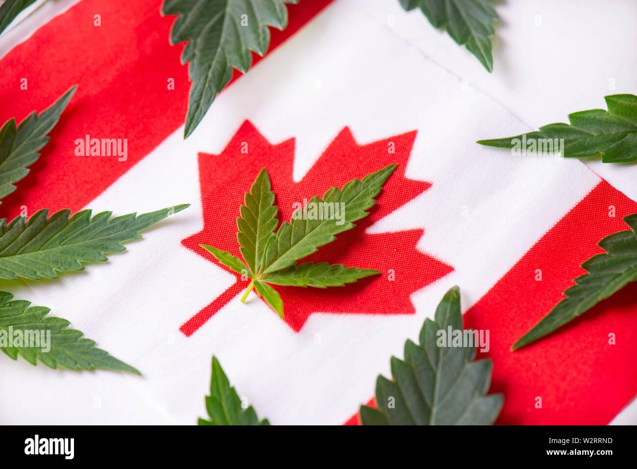 Canadian flag with cannabis leaf - canada marijuana concept background Stock Photo