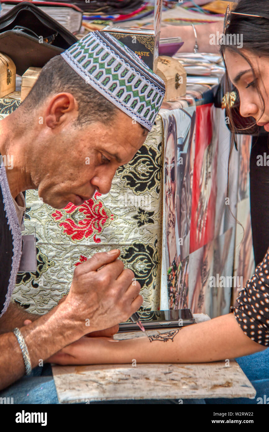 Mertola, Portugal - May 18, 2019: Moroccan craftsman making a henna tattoo on a girl in the streets of Mertola, where the Islamic festival is held eve Stock Photo