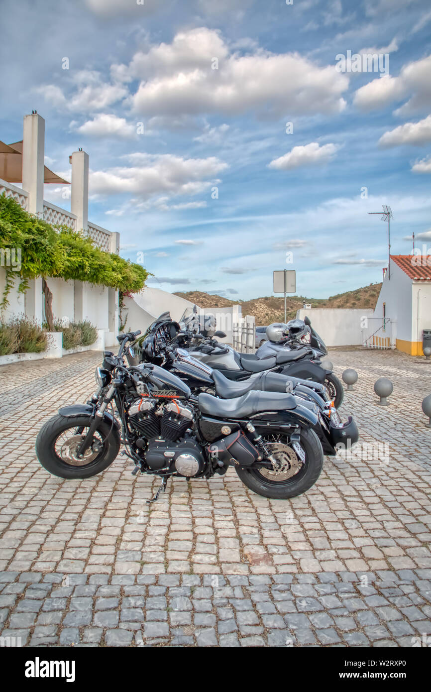 Mertola, Portugal - May 18, 2019: Motorcycles parked on a street in the beautiful city of Mertola, in the Portuguese Alentejo Stock Photo
