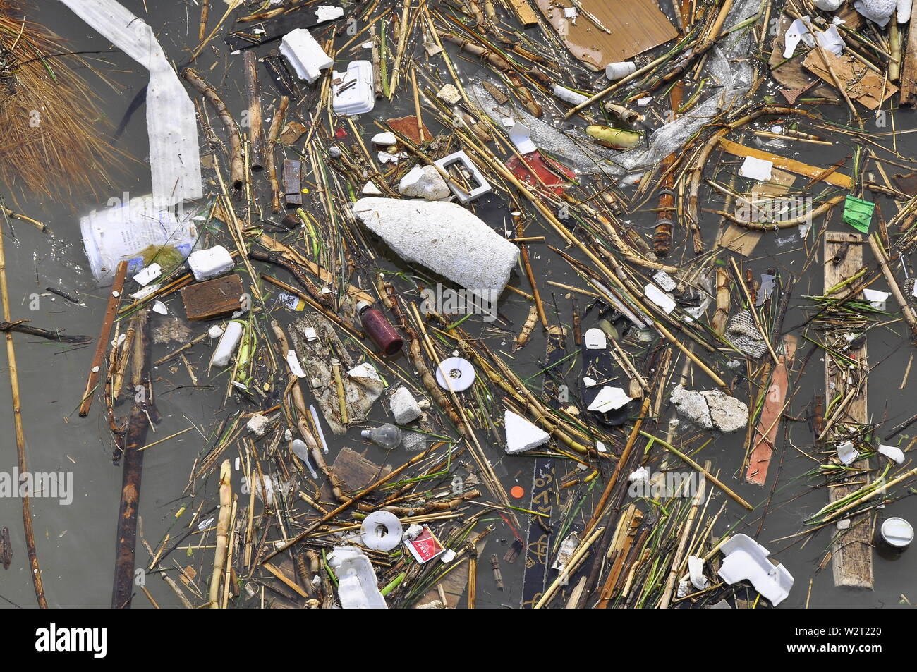 A variety of plastic and other waste products clog a river in China - Stock Image