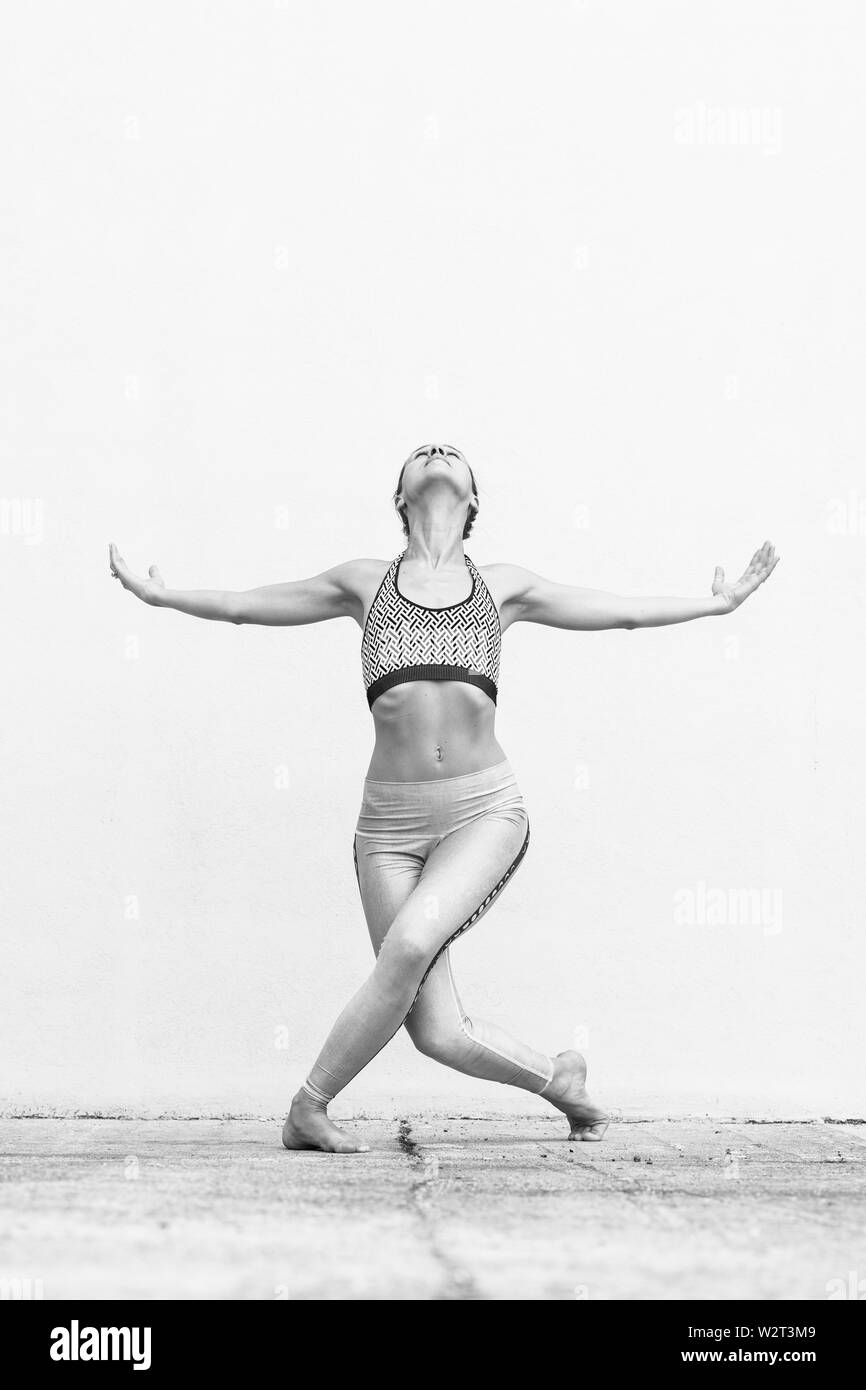 Fit sporty active girl in fashion sportswear doing yoga fitness exercise in front of gray wall, outdoor sports, urban style. Black and white image. - Stock Image