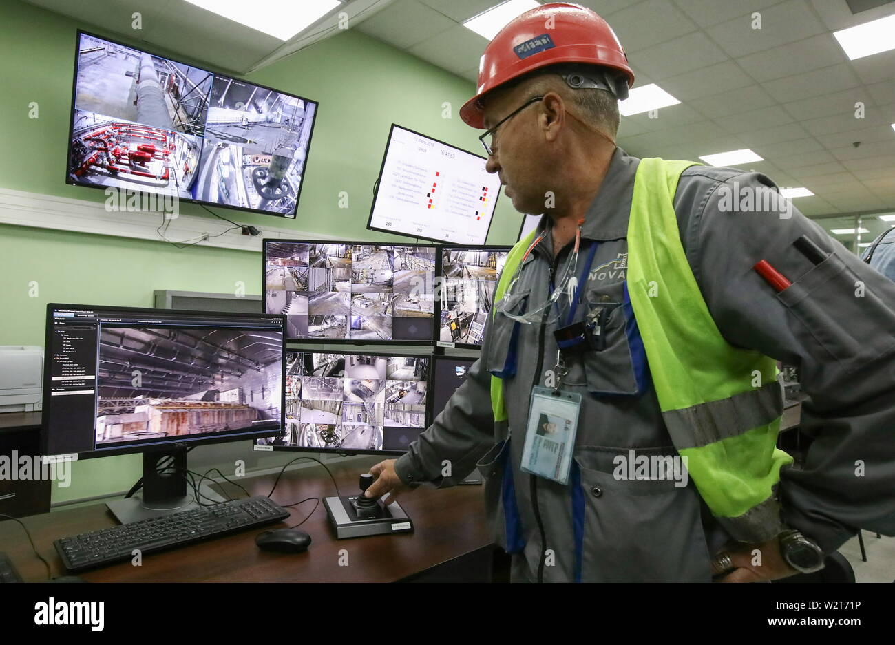 Pripyat, Ukraine. 10th July, 2019. PRIPYAT, UKRAINE - JULY 10, 2019: A worker in a safety helmet in a CCTV control room at the Chernobyl Nuclear Power Plant; the EU has officially handed over the new mobile metal structure, officially known as the New Safe Confinement, built over Reactor 4 of the Chernobyl Nuclear Power Plant to the Ukrainian authorities; the construction of the 1.5bn euro metal shelter began in 2012; Reactor 4 is the site of the 1986 Chernobyl disaster. Pyotr Sivkov/TASS Credit: ITAR-TASS News Agency/Alamy Live News - Stock Image