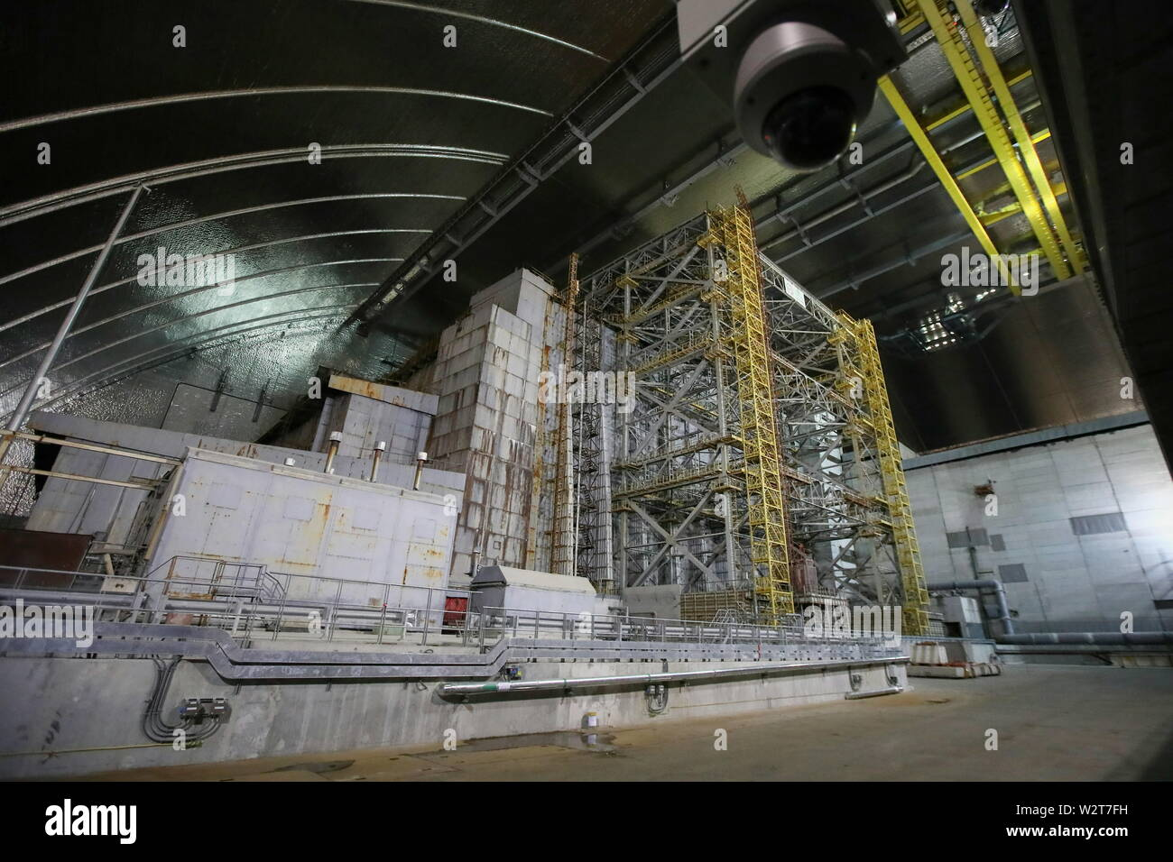 Pripyat, Ukraine. 10th July, 2019. PRIPYAT, UKRAINE - JULY 10, 2019: The image shows the older shelter protecting Reactor 4 of the Chernobyl Nuclear Power Plant under the new mobile metal structure, officially known as the New Safe Confinement, which has been officially handed over by the EU to the Ukrainian authorities; the construction of the 1.5bn euro metal shelter began in 2012; Reactor 4 is the site of the 1986 Chernobyl disaster; the older shelter is to be dismantled. Pyotr Sivkov/TASS Credit: ITAR-TASS News Agency/Alamy Live News - Stock Image