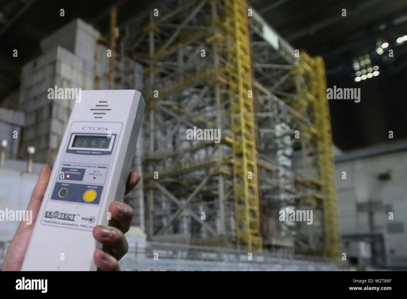Pripyat, Ukraine. 10th July, 2019. PRIPYAT, UKRAINE - JULY 10, 2019: The image shows a person using a dosimeter next to the older shelter protecting Reactor 4 of the Chernobyl Nuclear Power Plant, under the new mobile metal structure, officially known as the New Safe Confinement, which has been officially handed over by the EU to the Ukrainian authorities; the construction of the 1.5bn euro metal shelter began in 2012; Reactor 4 is the site of the 1986 Chernobyl disaster; the older shelter is to be dismantled. Pyotr Sivkov/TASS Credit: ITAR-TASS News Agency/Alamy Live News - Stock Image