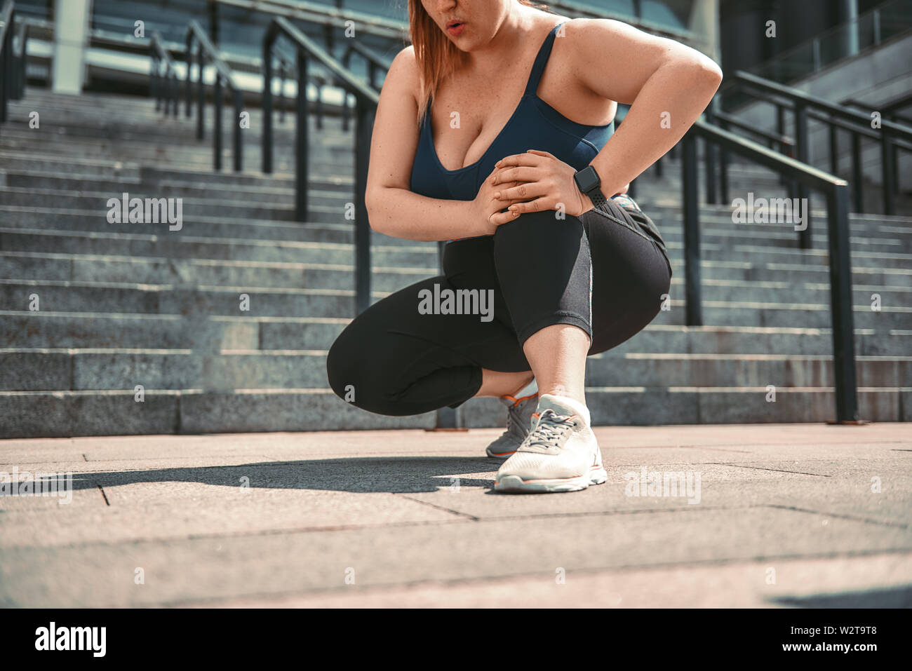 Feeling pain. Young plus size woman in sport clothes suffering from knee pain while standing on stairs. Sports injury. Weight losing. - Stock Image