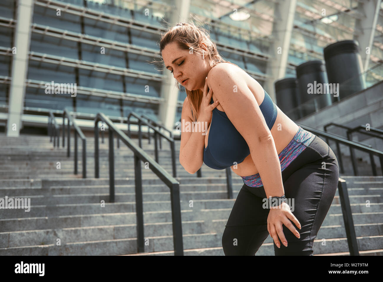 Pain after workout. Young plus size woman touching her shoulder and feeling pain after sport training while standing on stairs. Sports injury. Weight - Stock Image