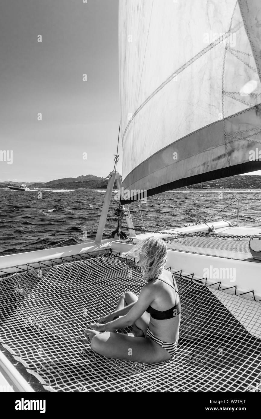 Beautiful woman relaxing on a summer sailing cruise, sitting and sunbathing in hammock of luxury catamaran sailing around Maddalena Archipelago, Sardi - Stock Image