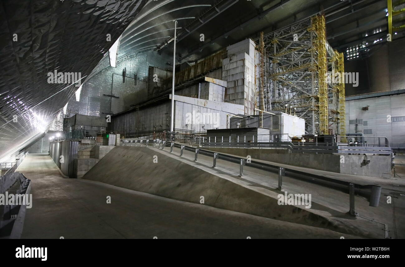 Pripyat, Ukraine. 10th July, 2019. PRIPYAT, UKRAINE - JULY 10, 2019: The image shows the older shelter protecting Reactor 4 of the Chernobyl Nuclear Power Plant, under the new mobile metal structure, officially known as the New Safe Confinement, which has been officially handed over by the EU to the Ukrainian authorities; the construction of the 1.5bn euro metal shelter began in 2012; Reactor 4 is the site of the 1986 Chernobyl disaster; the older shelter is to be dismantled. Pyotr Sivkov/TASS Credit: ITAR-TASS News Agency/Alamy Live News - Stock Image
