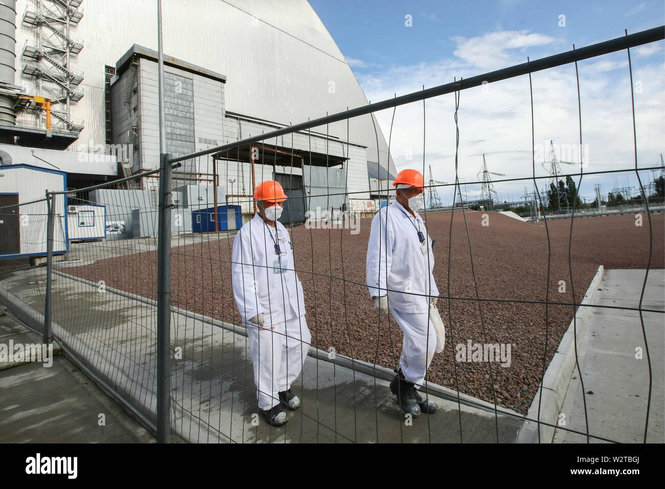 Pripyat, Ukraine. 10th July, 2019. PRIPYAT, UKRAINE - JULY 10, 2019: Workers outside the new mobile metal structure, officially known as the New Safe Confinement, built over Reactor 4 of the Chernobyl Nuclear Power Plant, the new metal shelter has been officially handed over by the EU to the Ukrainian authorities; the construction of the 1.5bn euro metal shelter began in 2012; Reactor 4 is the site of the 1986 Chernobyl disaster. Pyotr Sivkov/TASS Credit: ITAR-TASS News Agency/Alamy Live News - Stock Image