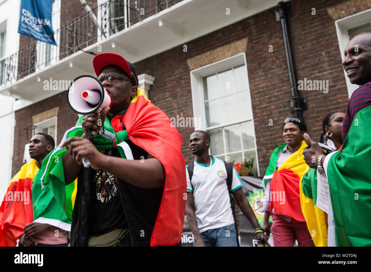 London, UK. 10 July, 2019. Members of the Senegalese community in the UK who support Senegalese civil society movement Aar Li Ñu Bokk protest outside Chatham House during an interview by Evan Davis of BP Group Chief Executive Bob Dudley to discuss balancing increasing energy needs  with climate change considerations. The protest followed a BBC Panorama exposé on a $10bn petrol and gas corruption scandal in Senegal for which they hold BP accountable, as well as the awarding of an oil exploitation contract through Timis Corporation. Credit: Mark Kerrison/Alamy Live News - Stock Image