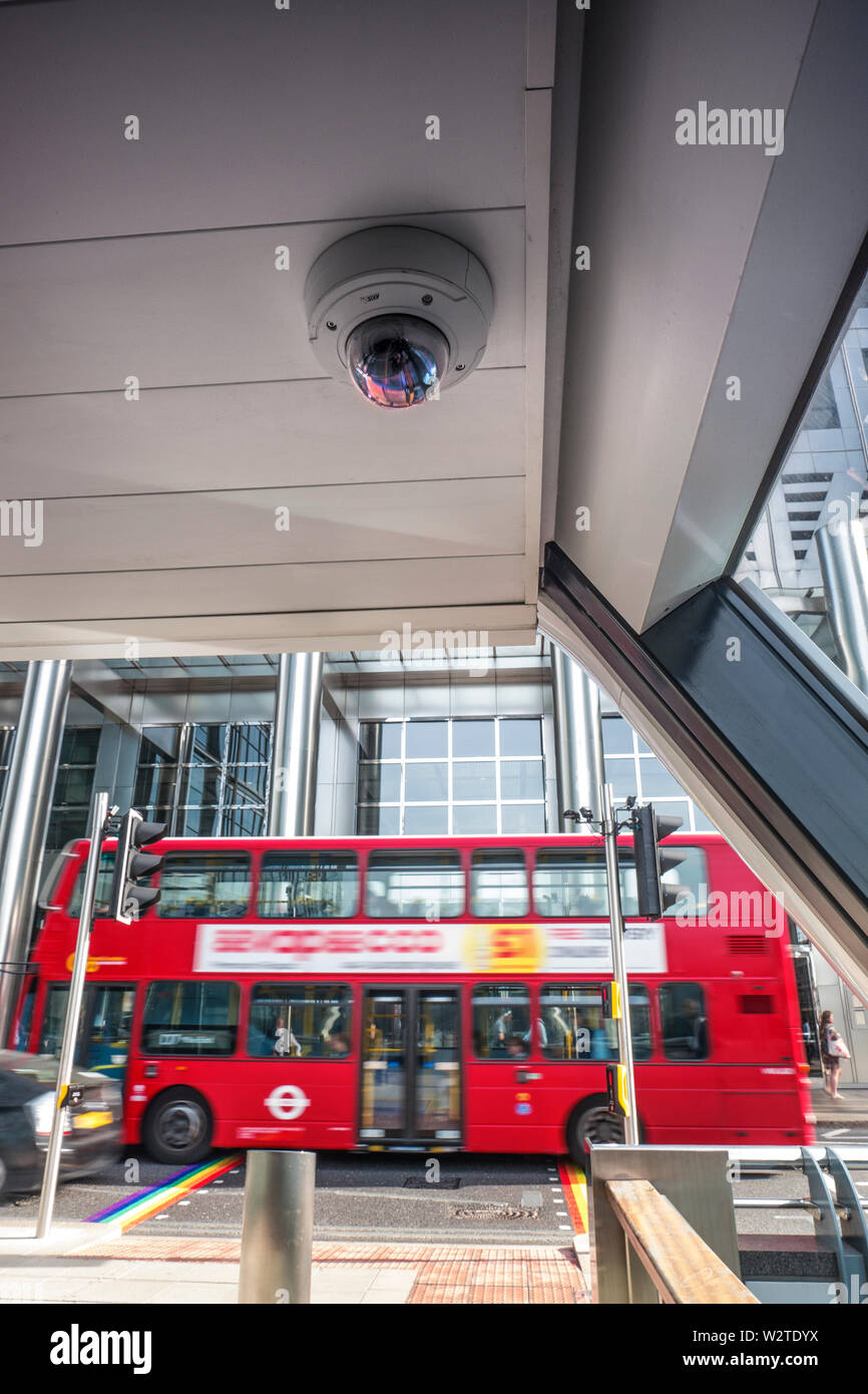 CCTV surveillance security network camera in Canary Wharf with traditional red London Bus behind. A 360 degree state of the art, closed security camera system which records illegal, anti-social behaviour and alerts for immediate action Canary Wharf London E14 - Stock Image