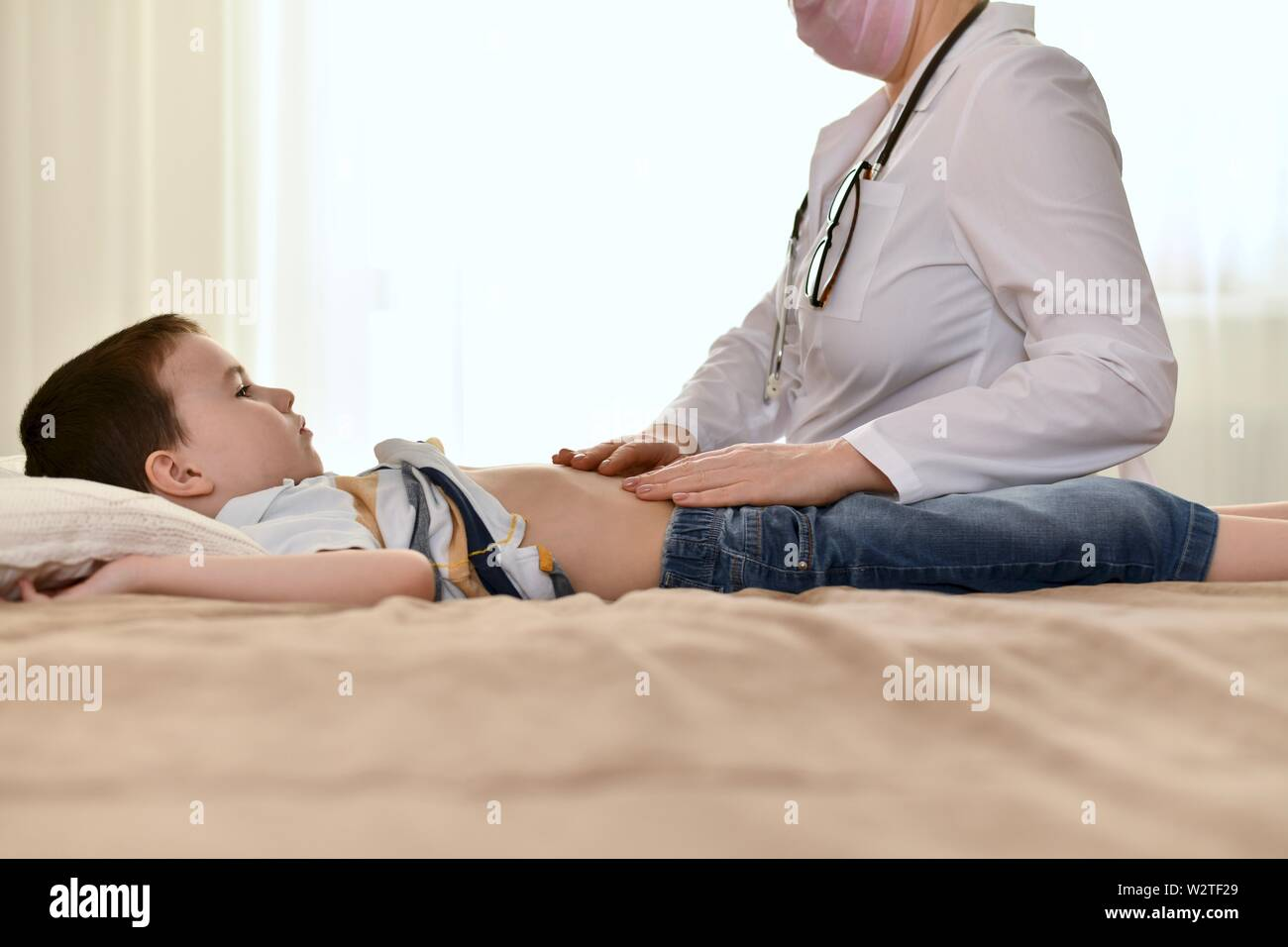 The doctor examines the belly of a sick child at home. A boy with a sad, serious face is lying on the bed and looking at the stethoscope on her neck. Stock Photo
