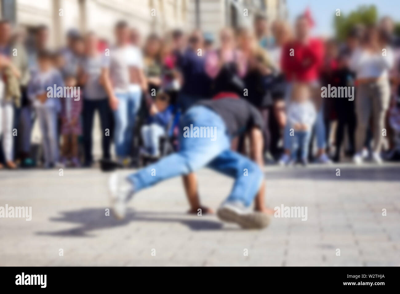 Strong blur, anonymous people on the streets of Europe. Street break dance show - Stock Image