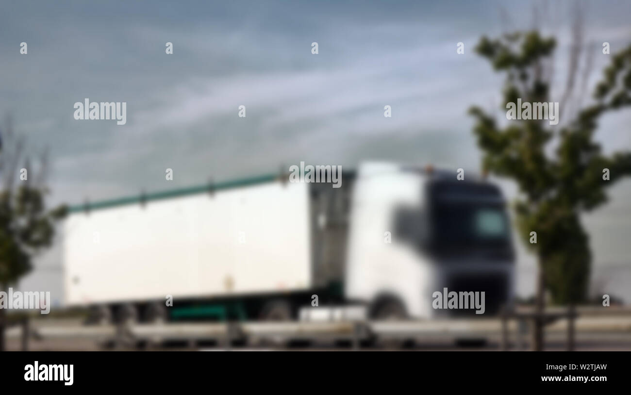 Strong blurred unrecognizable truck transport on road. Transport overpasses on the highway for the transport of orders and goods - Stock Image