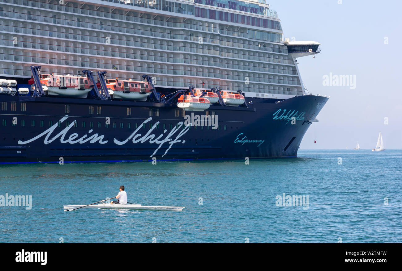 TRIESTE, Italy - June 16, 2019: Rower in front of the cruise ship Mein Schiff 6 moored next to Audace pier on the city's seafront - Stock Image