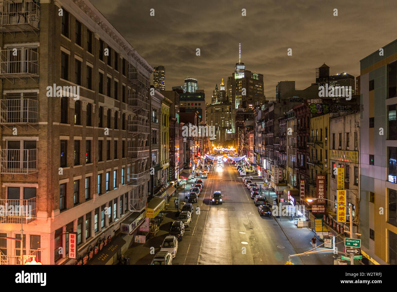 Manhattan bridge view over Chinatown at night, lower Manhattan in the background. New York City, United States of America. - Stock Image