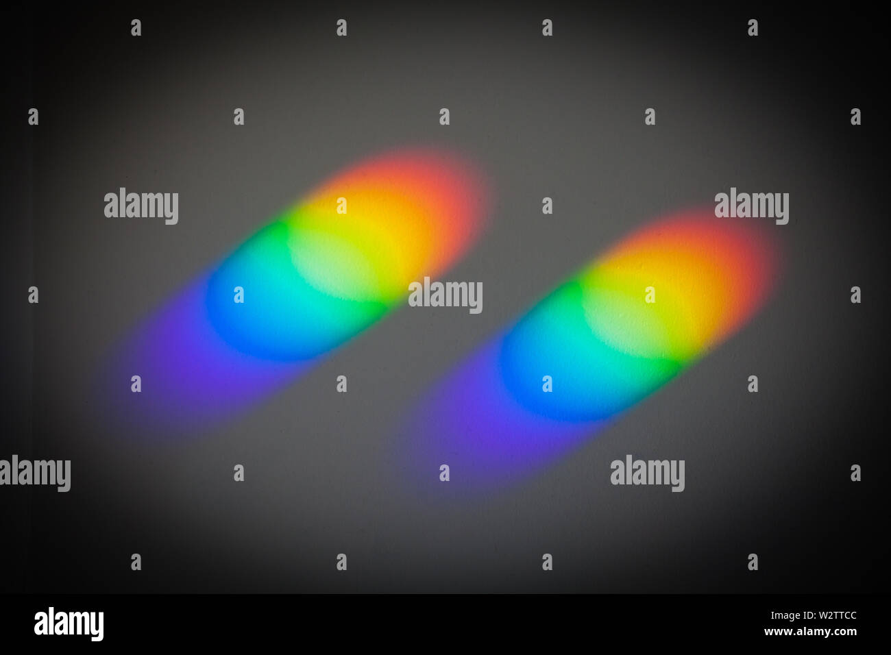 Rainbow Colours on the ceiling, caused by sunlight passing through small prisms on the windowsill. 'Colour & Texture'. The prisms come from binoculars - Stock Image