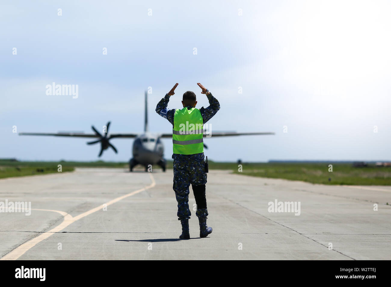 Boboc, Romania - May 22, 2019: Ground personnel is aircraft marshalling an Alenia C-27J Spartan military cargo plane from the Bulgarian Air Force that Stock Photo