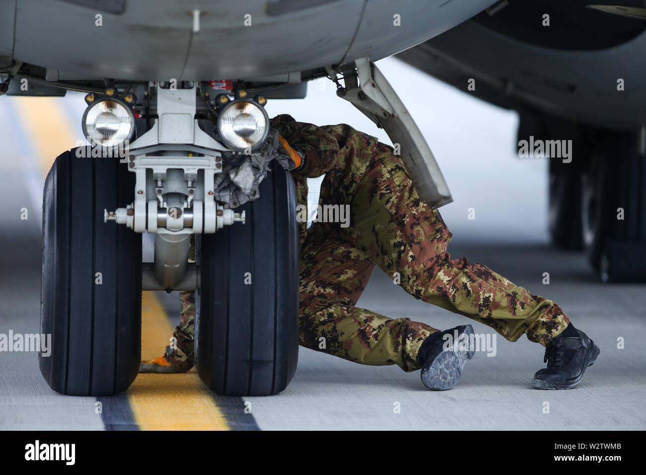 Otopeni, Romania - May 22, 2019: A mechanic is inspecting parts of an Alenia C-27J Spartan military cargo plane after landing on an airbase. - Stock Image