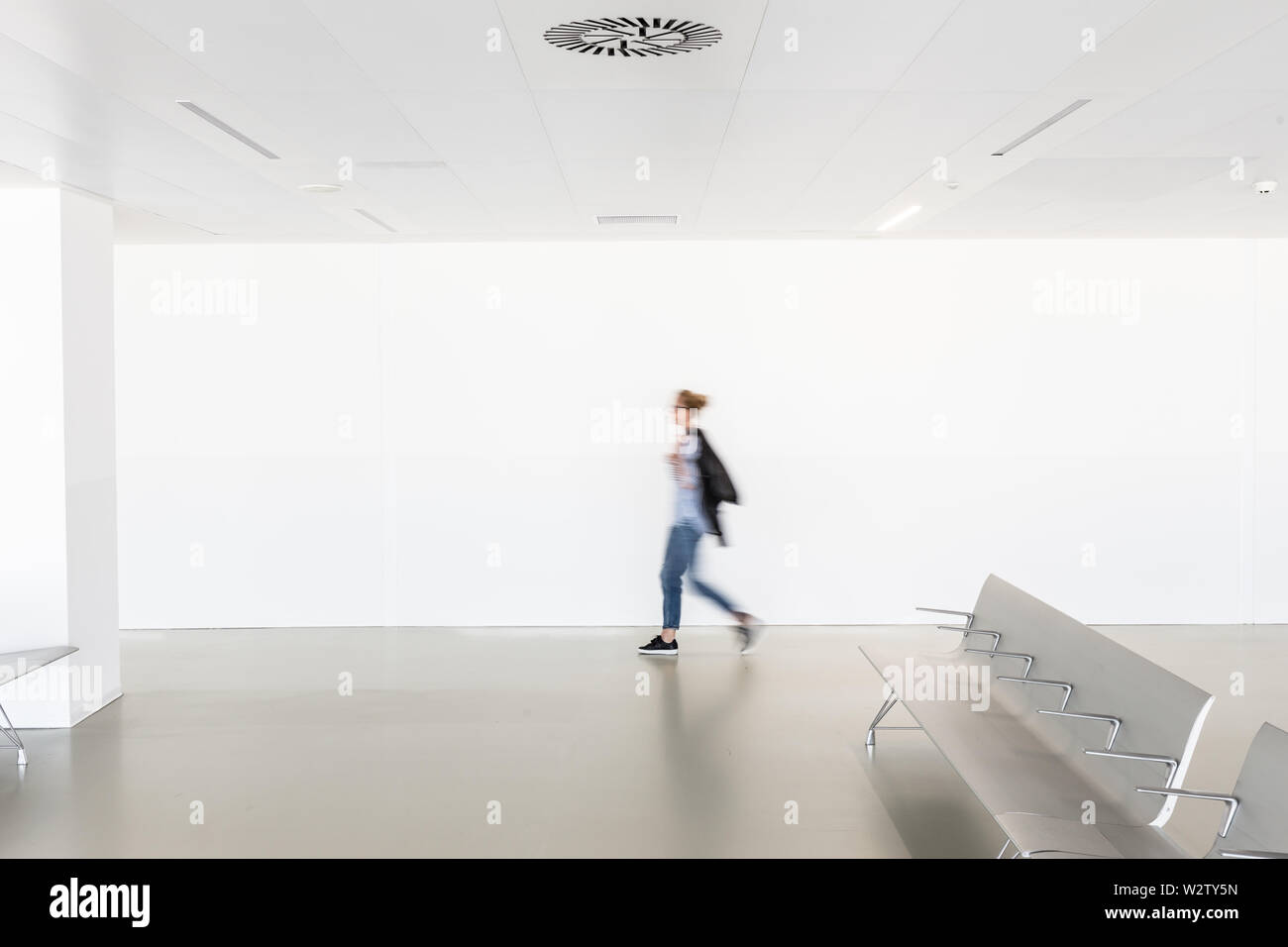 Motion blur of woman walking at contemporary white empty hallway. - Stock Image