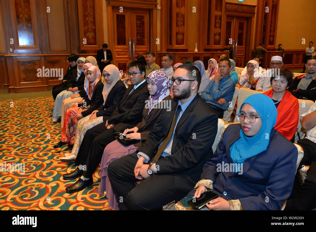(190710) -- BANDAR SERI BEGAWAN, July 10, 2019 (Xinhua) -- Scholarship recipients and their parents attend a graduation ceremony for the fifth batch of 11 scholarship students under the Joint Chemical and Process Engineering Scholarship Program provided by Hengyi Industries Sdn Bhd, in Bandar Seri Begawan, capital of Brunei, July 10, 2019. Hengyi Industries Sdn Bhd, a China-Brunei joint venture, hopes to provide at least 50 percent of over 2,000 new jobs to local Bruneians in the second phase of Pulau Muara Besar (PMB) refinery and petrochemical plant, Li Peng, director of General Affairs of H - Stock Image