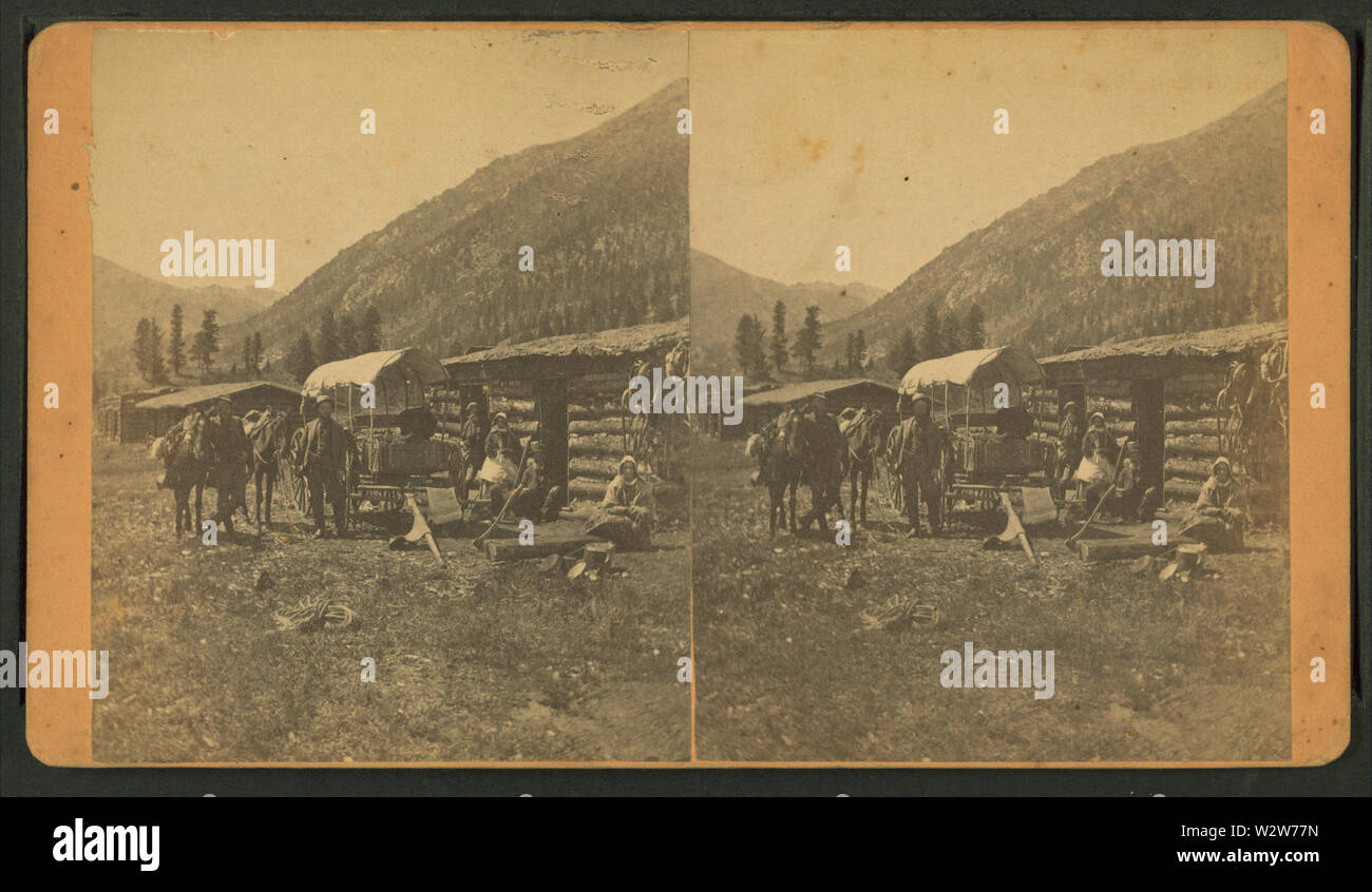 Group in front of a log cabin with a covered wagon, by C W Talbot - Stock Image