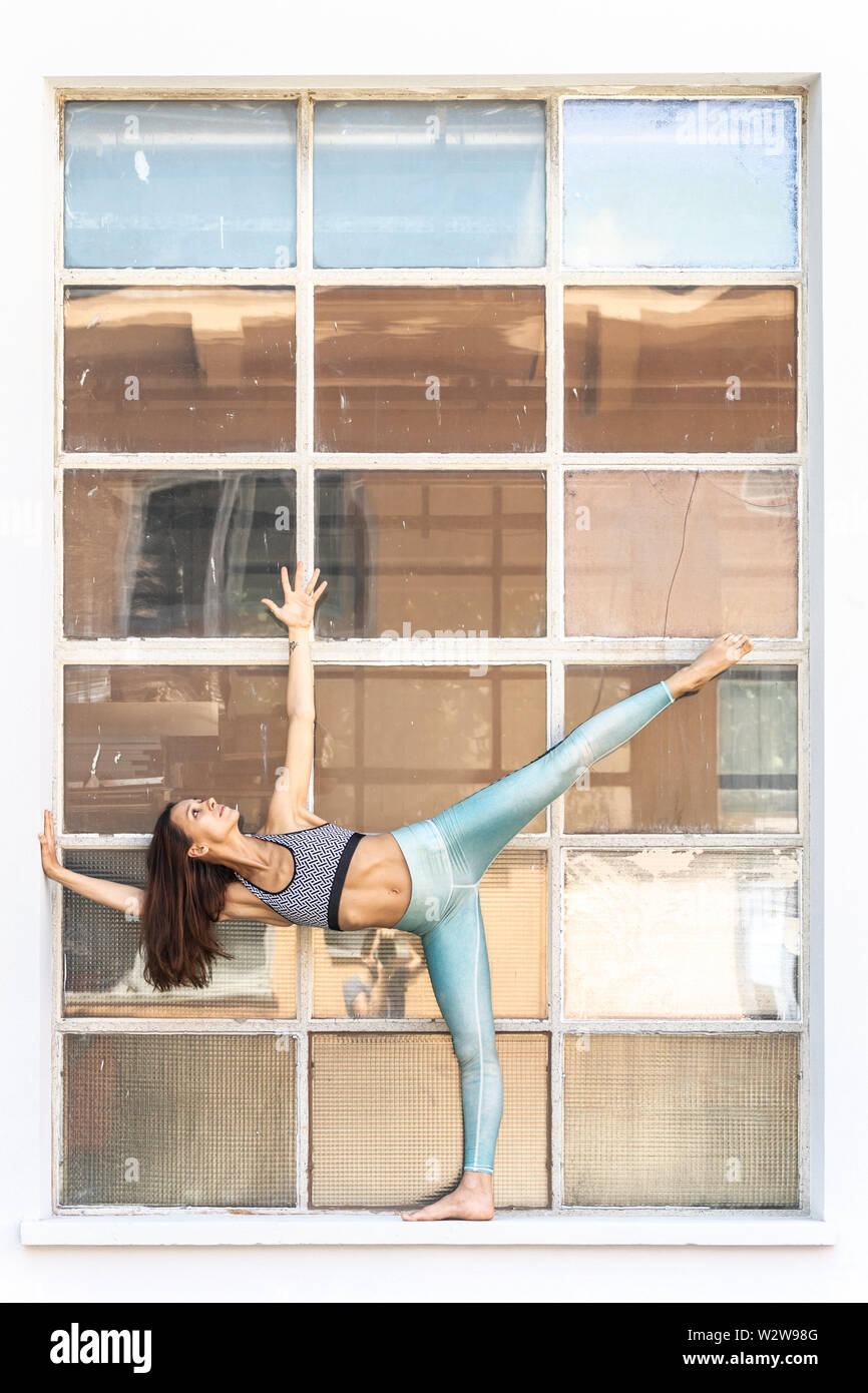 Fit sporty active girl in fashion sportswear doing yoga fitness exercise in front of big industrial window frame. colorful reflections in window glass - Stock Image