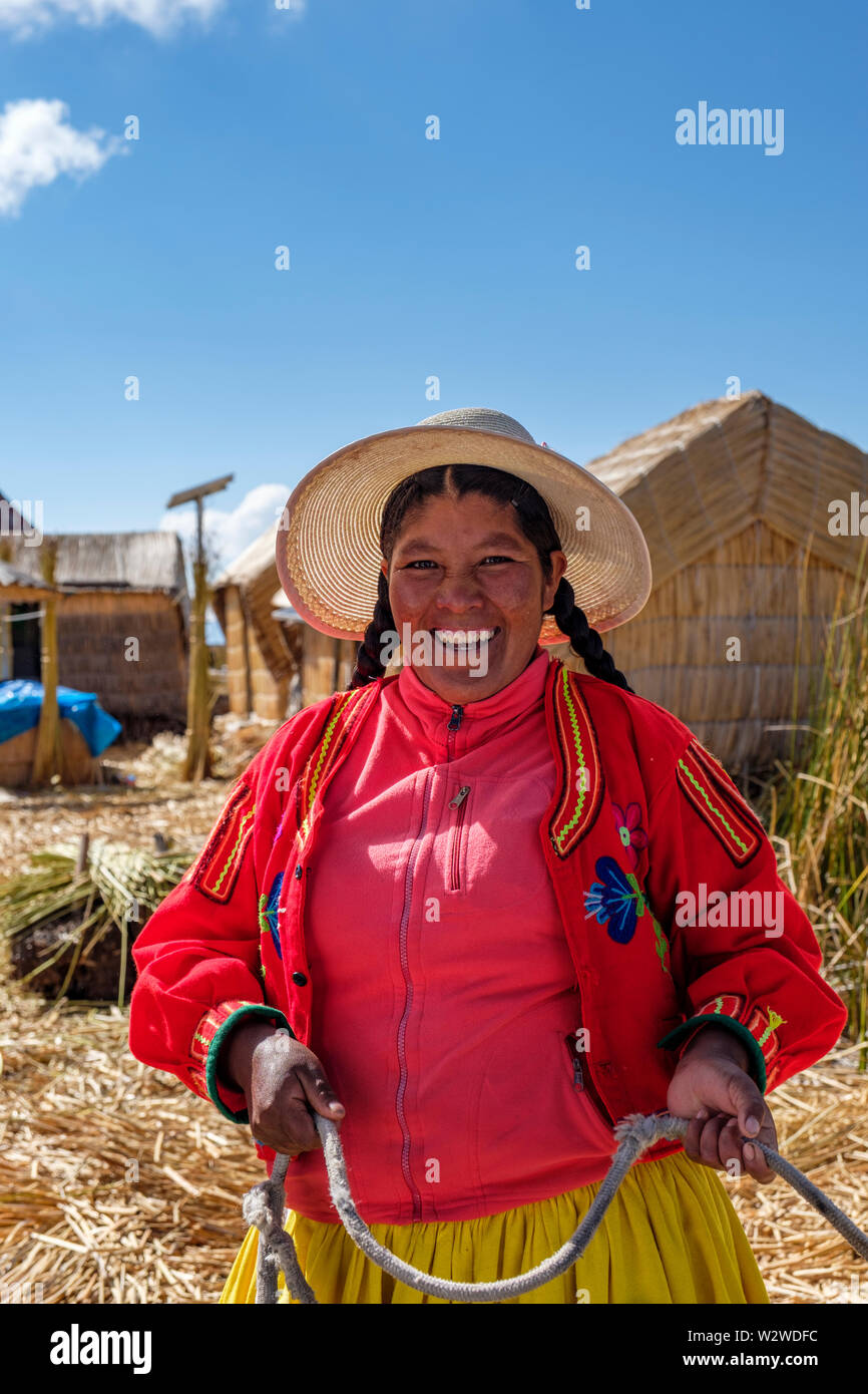 Portrait of a smiling local Uru woman greeting visitors to a totora reed floating island, Uros Floating Islands, Lake Titicaca, Uros, Peru. - Stock Image