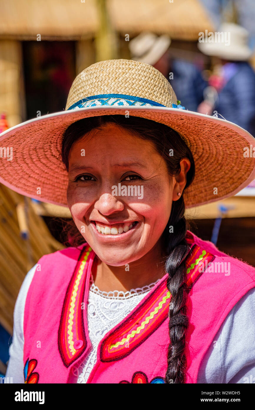 Portrait of a smiling local Uru woman in a totora reed floating island, Uros Floating Islands, Lake Titicaca, Uros, Peru. - Stock Image